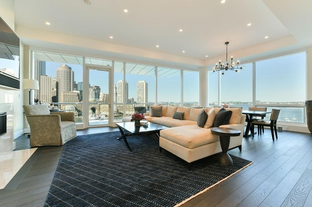 A sweeping corner living room with furniture and floor-to-ceiling windows with harbor views.