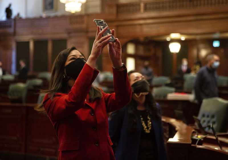 State Rep. Denyse Wang Stoneback, D-Skokie, takes a picture of a roll call on the video board in February.