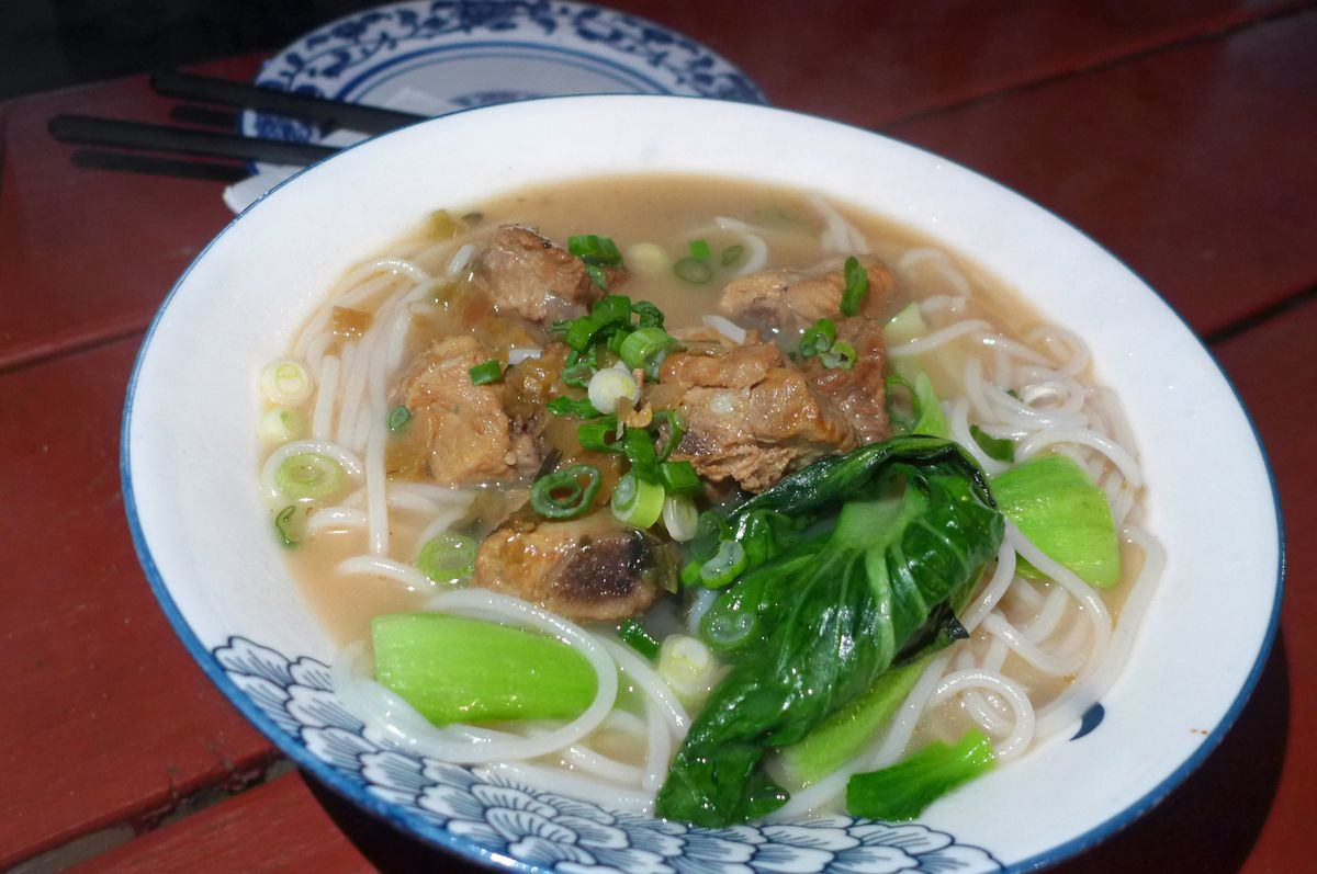 A bowl of noodle soup with hunks of pork.
