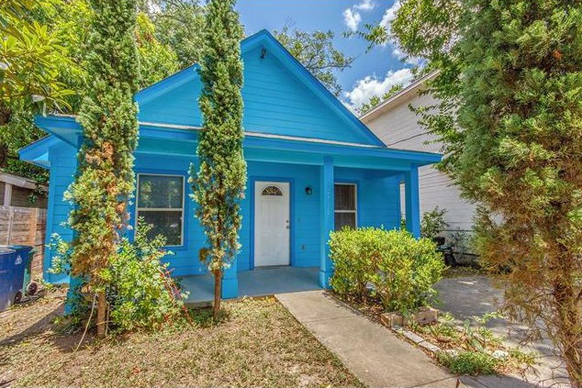 Bright blue wooden cottage with Italian cypress in front