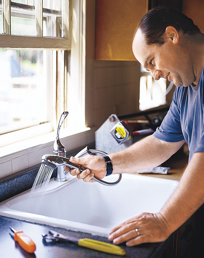 Man Testing Faucet With Sprayer