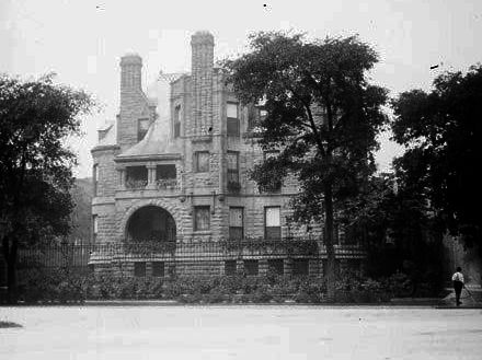 A large mansion with towers. There is an arched entryway.