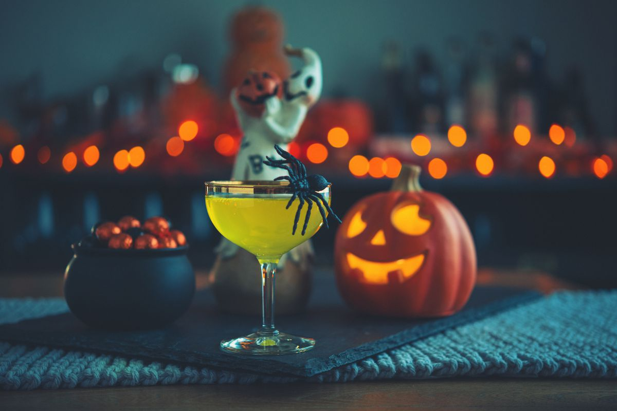 """a """"Halloween"""" themed cocktail in a glass surrounded by lit jack-o'-lanterns"""