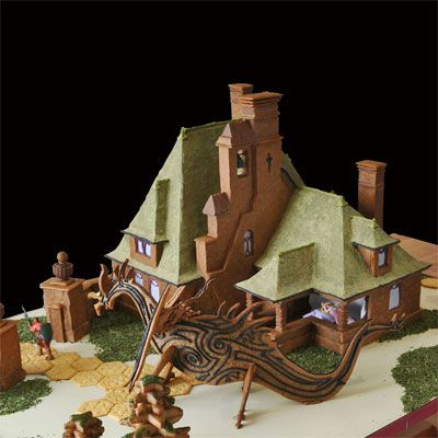 A gingerbread castle complete with a gingerbread dragon sitting outside.