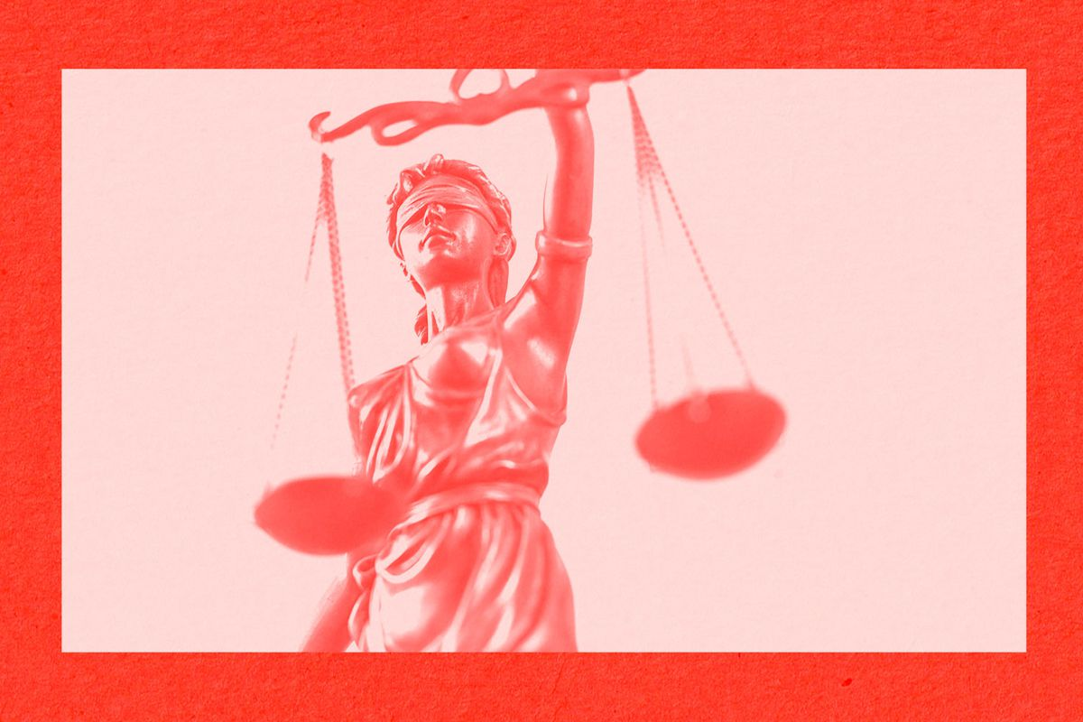 A statue of justice holding a scale over a red background