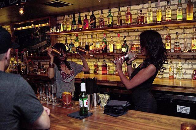Bartenders shake drinks behind a bar