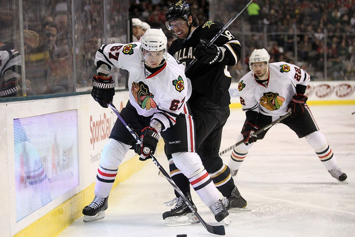 Right wing Michael Frolik of the Chicago Blackhawks skates the puck against James Neal of the Dallas Stars at American Airlines Center on February 11 2011 in Dallas Texas.  (Photo by Ronald Martinez/Getty Images)