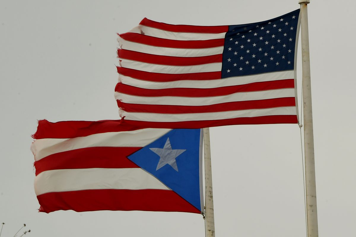 The flags of Puerto Rico and the US flying side by side on flagpoles.