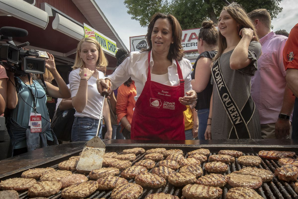 Kamala Harris dons a red apron and flips pork burgers at the Pork Association tent.