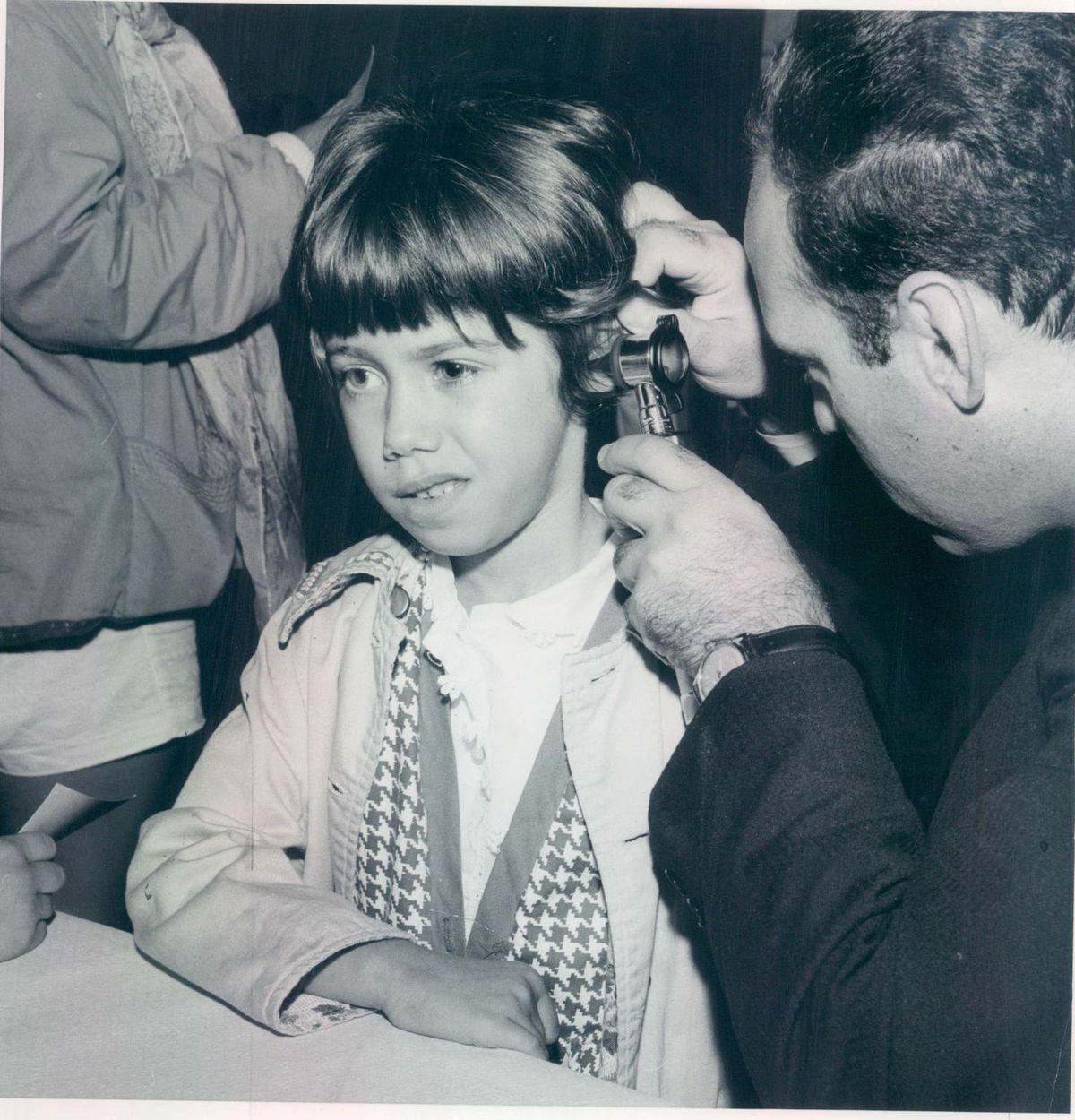 Dr. Benjamin Emanuel examines a 6-year-old girl in a pre-camp physical in 1962.