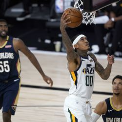 Utah Jazz's Jordan Clarkson (00) heads to the basket as New Orleans Pelicans' E'Twaun Moore (55) and Josh Hart defend during the second half of an NBA basketball game Thursday, July 30, 2020, in Lake Buena Vista, Fla. (AP Photo/Ashley Landis, Pool)