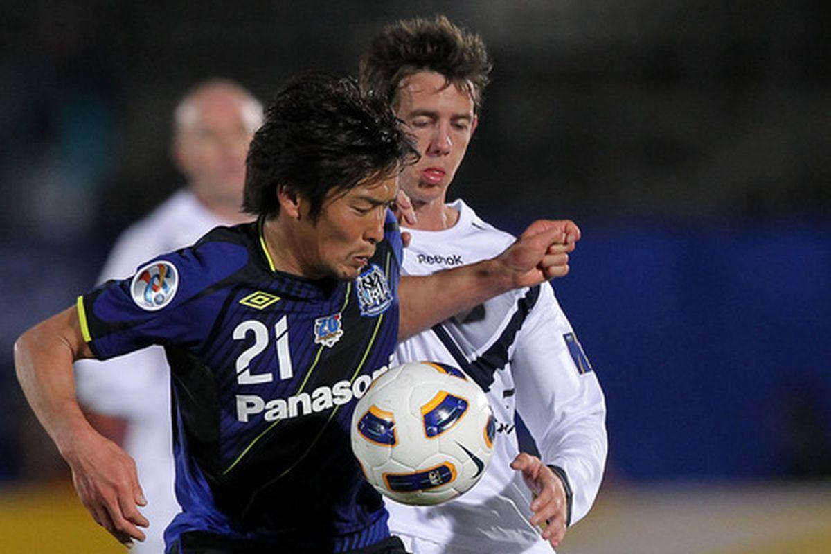 Kaji (left) in action with Gamba Osaka