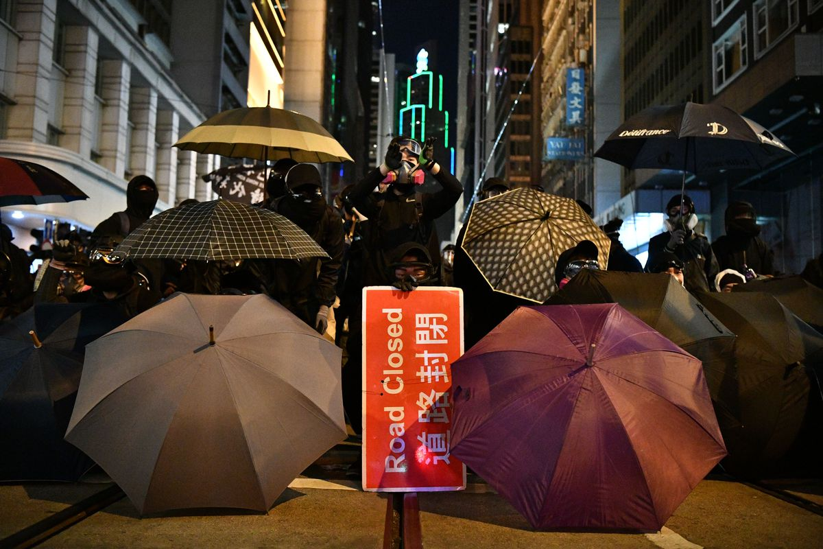 "Black-clad protesters hold umbrellas and a sign saying ""Road Closed"" in front of building lit up for the night."