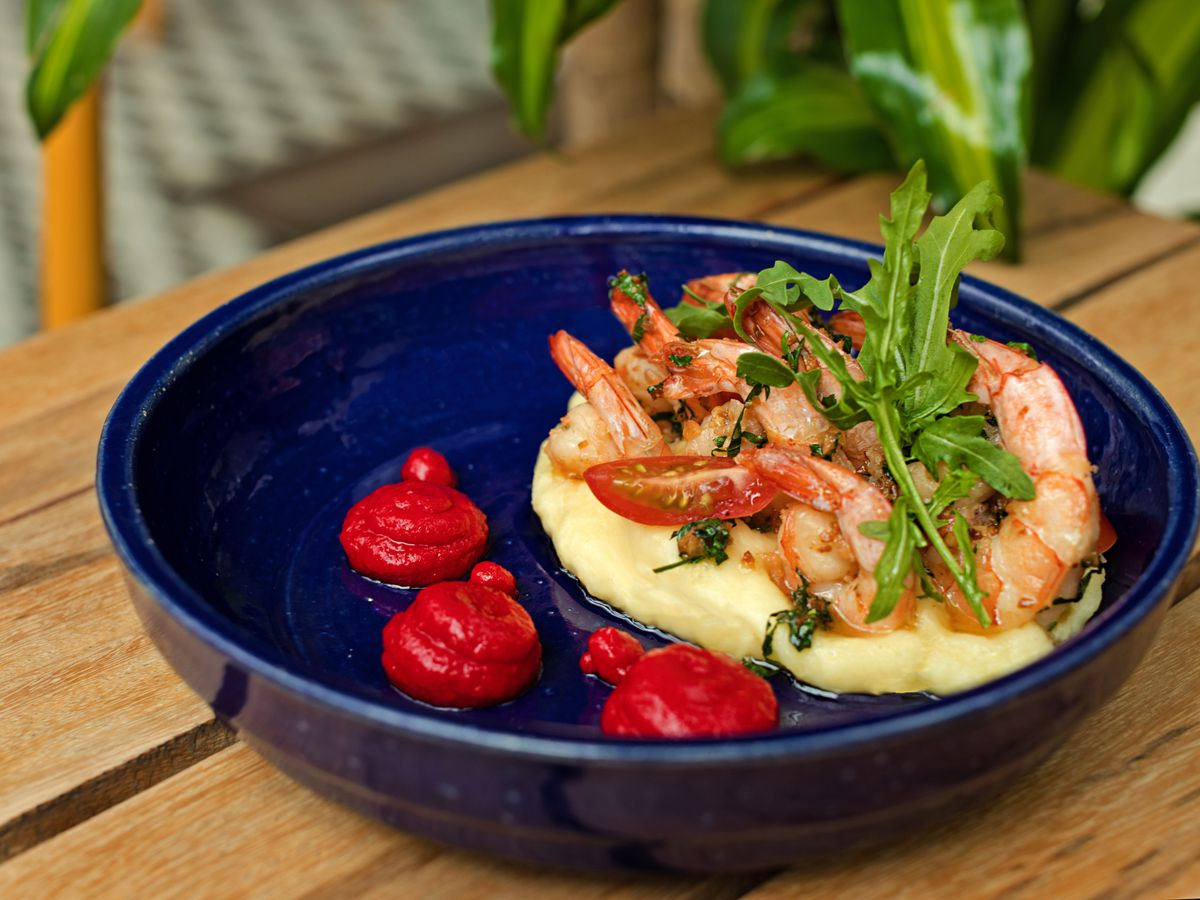Cooked shrimp sit with tomato and sprigs of greens on a pile of mashed cassava in a ceramic bowl beside three smaller spots of sauce, all on a wood table