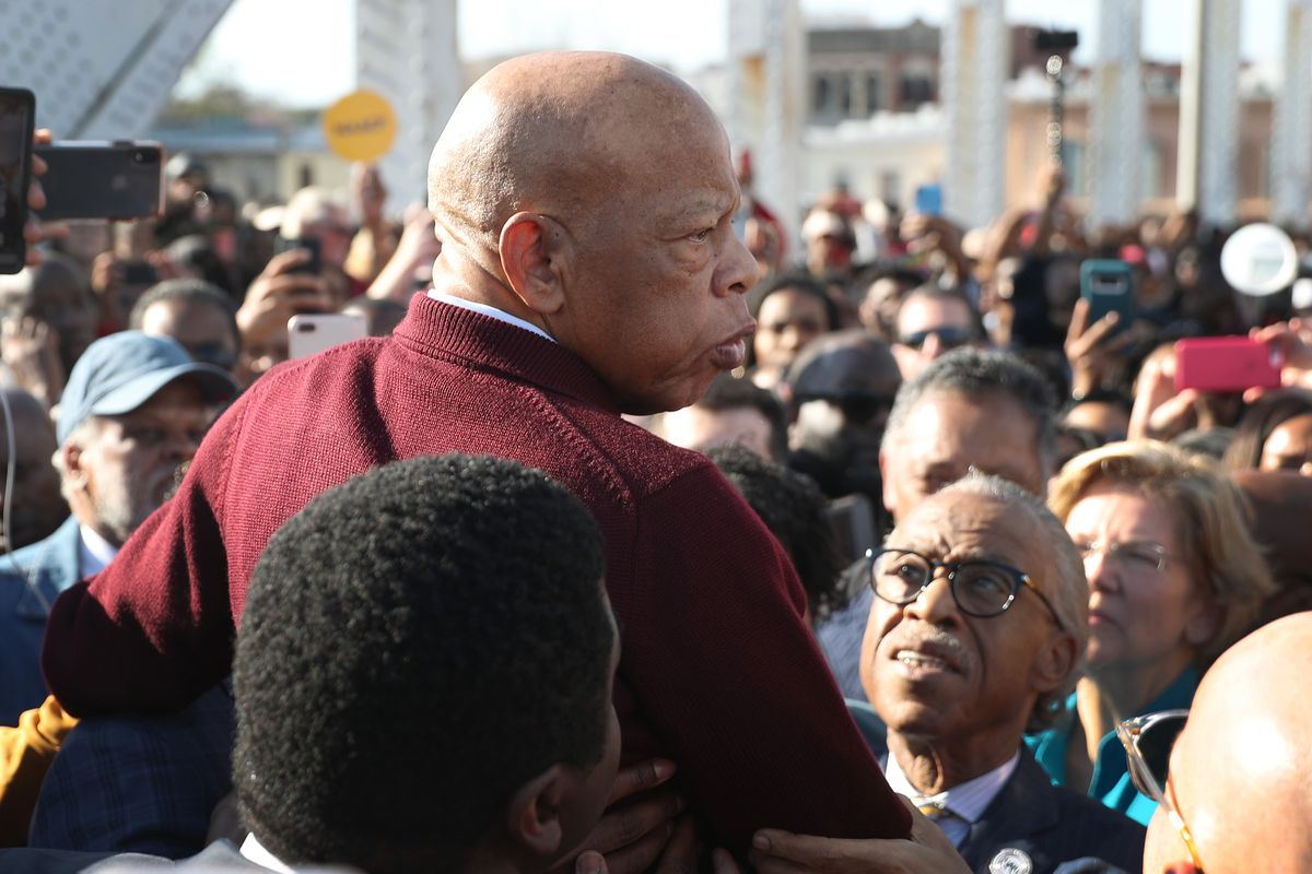 Lewis, his head shaved and in a maroon sweater, looks around him. His head is to the right; all around him are supporters, activists, and politicians. He is slightly elevated — people are raising him up. In front of him, Al Sharpton and Sen. Elizabeth Warren look up at him.