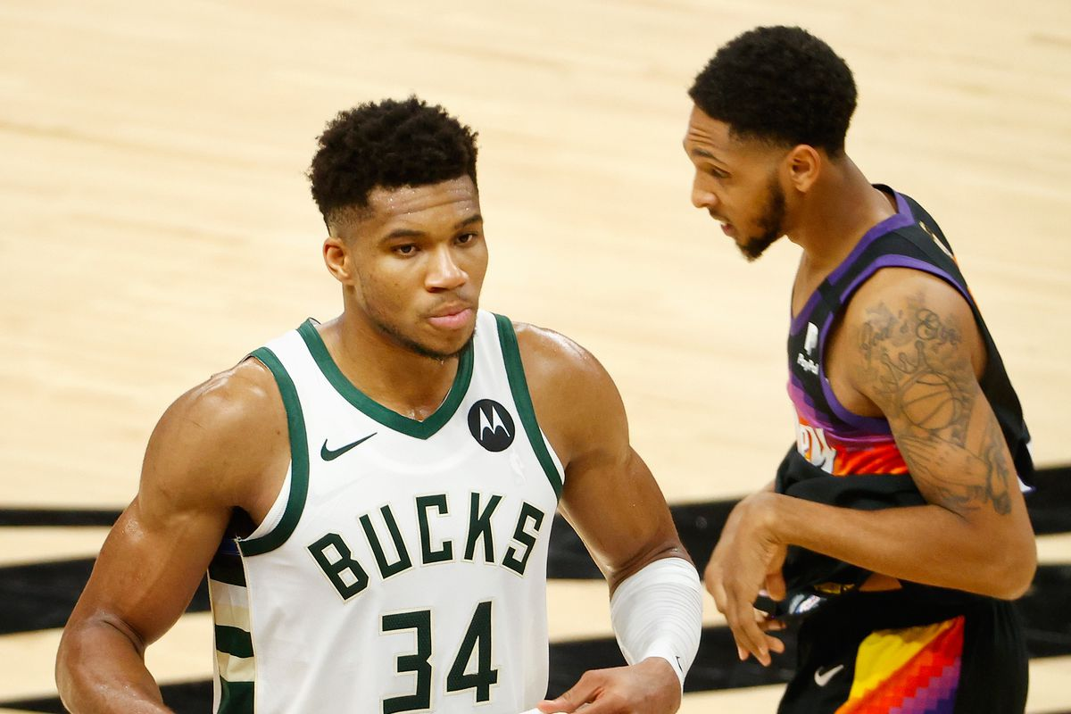 Giannis Antetokounmpo of the Milwaukee Bucks walks off the court past Cameron Payne of the Phoenix Suns following game two of the NBA Finals at Phoenix Suns Arena on July 08, 2021 in Phoenix, Arizona. The Suns defeated the Bucks 118-108.