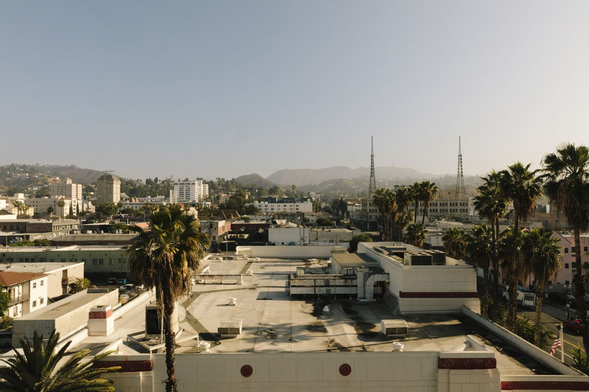 Aerial view of palm trees and rooftops of buildings with various heights. In the foreground, radio towers and hills.