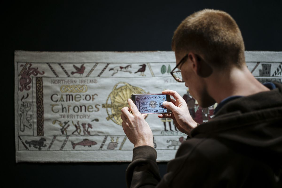 """A man takes a picture of the """"Game of Thrones"""" tapestry in Bayeux, Normandy, France."""