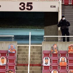 A security guard stands above cutouts of fans in the stands as Utah and Oregon State prepare to play a college football game at Rice-Eccles Stadium in Salt Lake City on Saturday, Dec. 5, 2020.