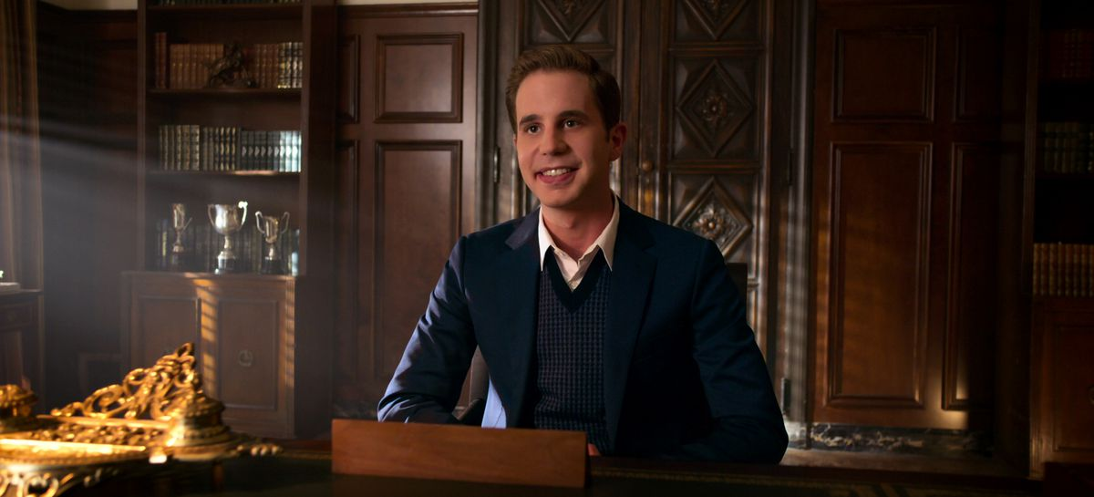 ben platt sits in the principal's office, with an eager smile