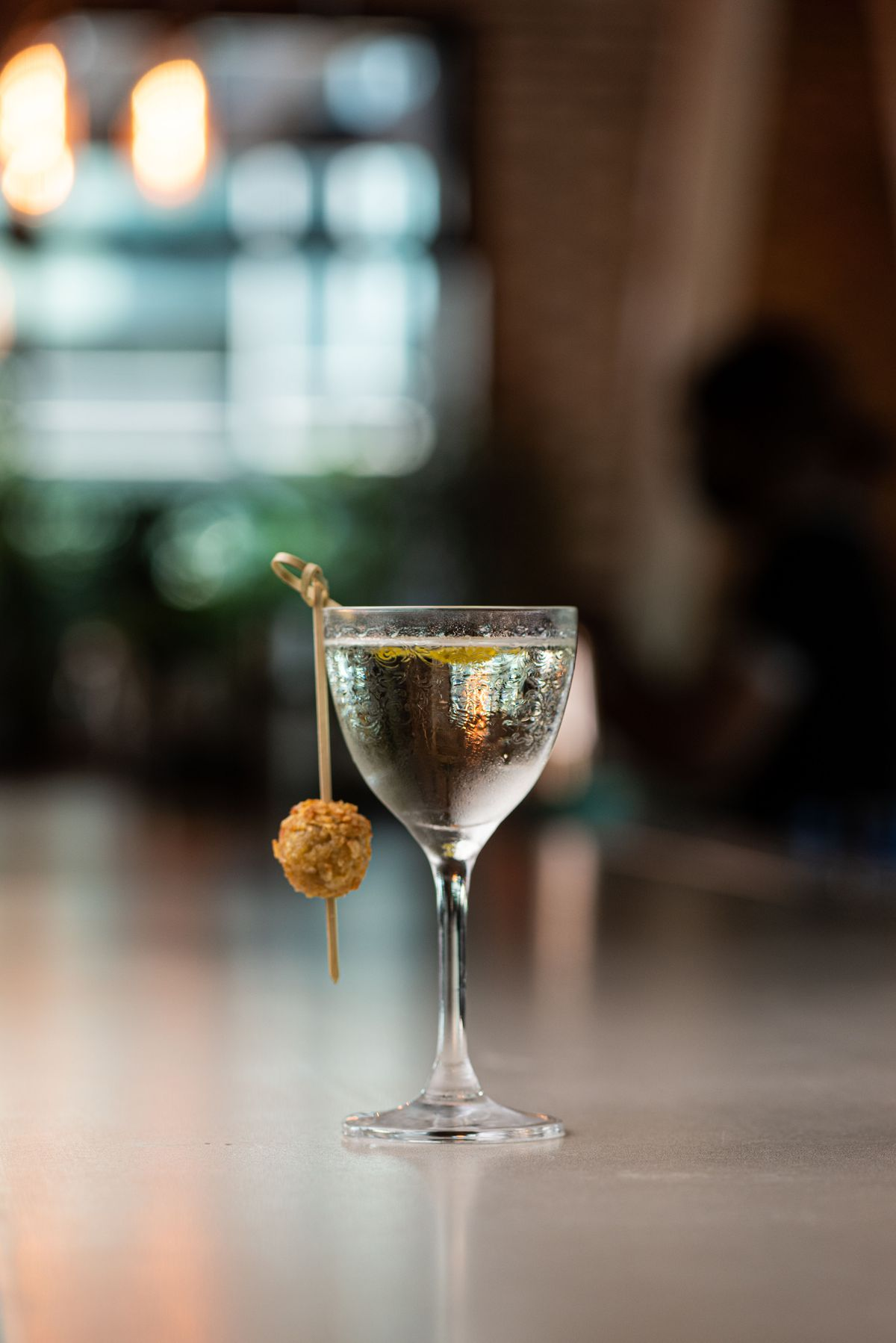 A clear cocktail with a hanging garnish in a glass.