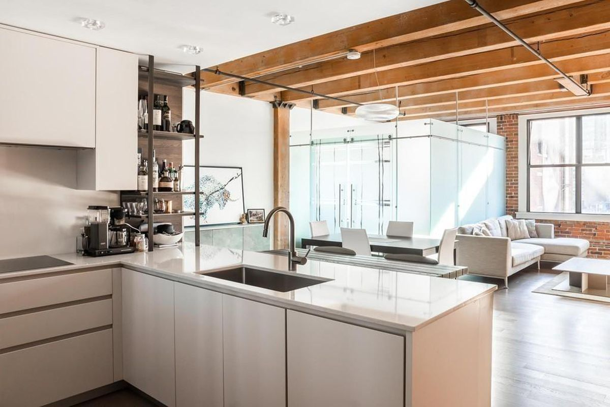 An open kitchen-living room area with a glass-enclosed bedroom in the background.