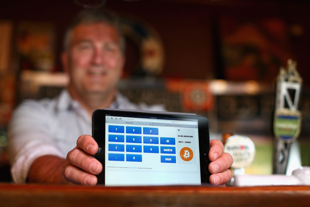 A barman at a Sydney pub shows a tablet screen that accepts bitcoin as payment for drinks.