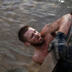 A competitor emerges from the tyre crawl during the Tough Guy Challenge on January 27, 2013 in Telford, England.