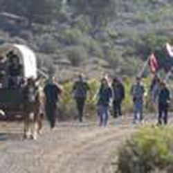 A horse-drawn wagon leads descendants carrying banners with the Mountain Meadows Massacre victim's famly names to an event marking the 150th anniversary of the Mountain Meadows Massacre at the memorial site near Enterprise.