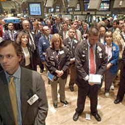 People on the floor of the New York Stock Exchange on Thursday pause for a moment of silence at 10:29 a.m., the time the second tower fell in 2001.
