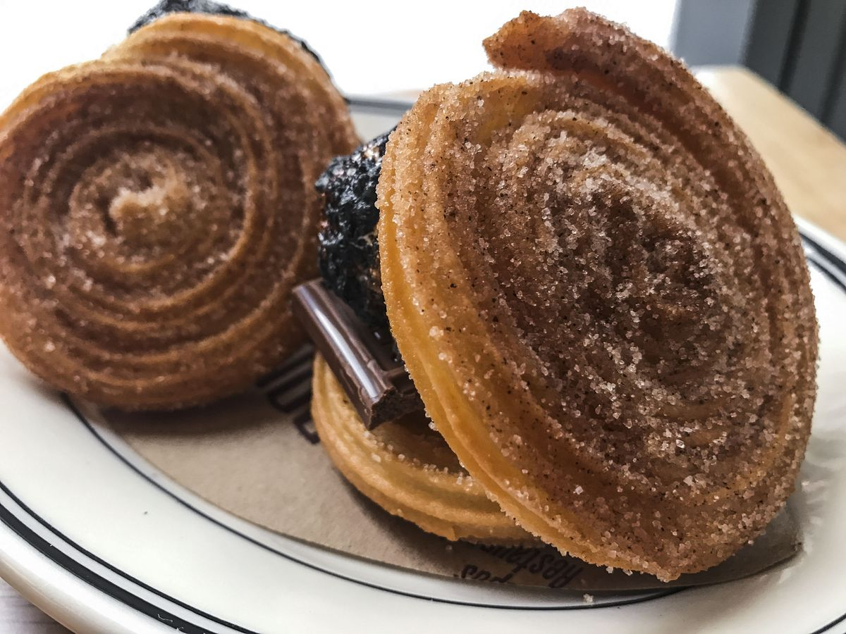 Two swirl pastries covered in cinnamon and sugar