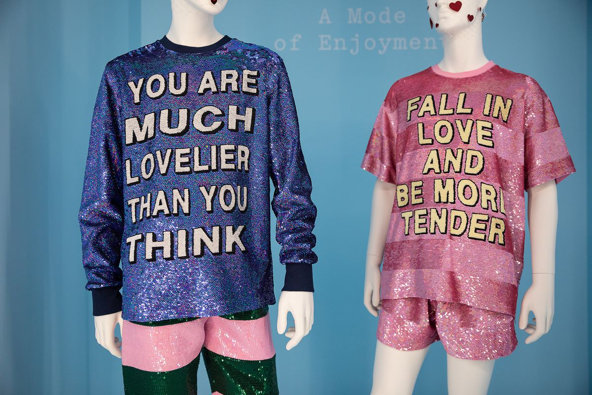 """Two glittery shirts, one of which says """"You are much lovelier than you think"""" and the other """"Fall in love and be more tender."""""""