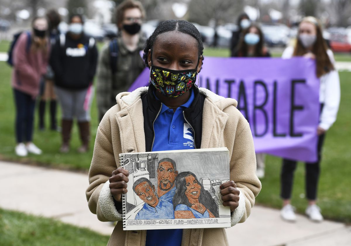A young woman wearing a cream colored jacket, blue shirt and cloth mask holds a drawing of Ahmaud Arbery, George Floyd and Breonna Taylor.  Students hold a purple banner behind her.