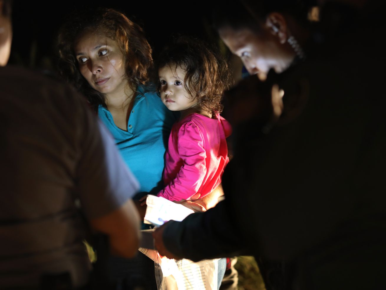 A Honduran mother holds her 2-year-old as US Border Patrol as agents review their papers near the US-Mexico border on June 12, 2018, in McAllen, Texas.