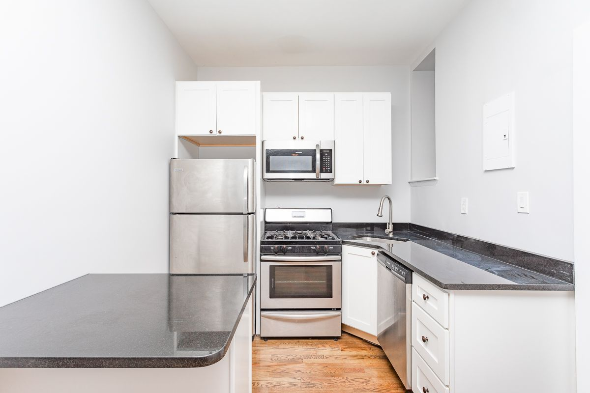 A kitchen with a small island, hardwood floors, and white cabinetry.