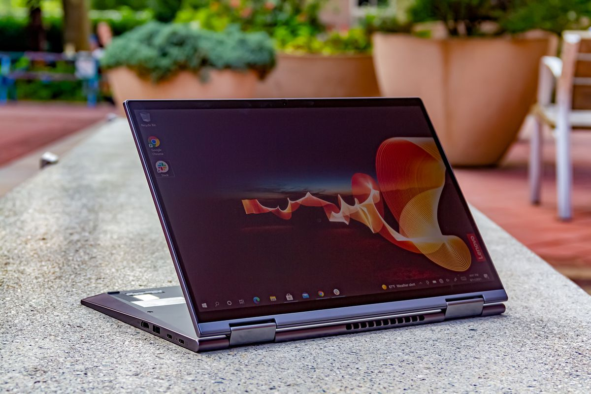 The Lenovo ThinkPad X1 Yoga Gen 6 in easel mode angled to the left on a stone outdoor bench. The screen displays an outdoor night scene with an orange banner rippling through and the Lenovo banner on the bottom right side.