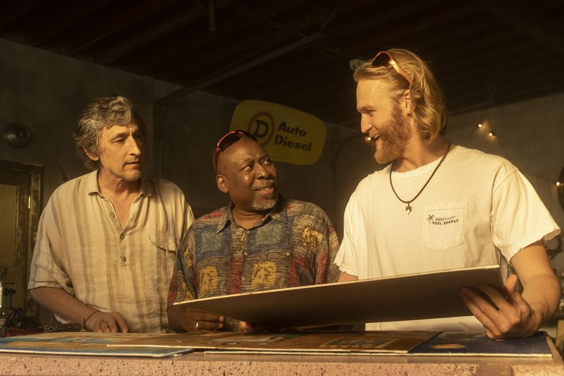 "Three actors on ""Lodge 49"" looking at one another and at a large board held in one character's hands."
