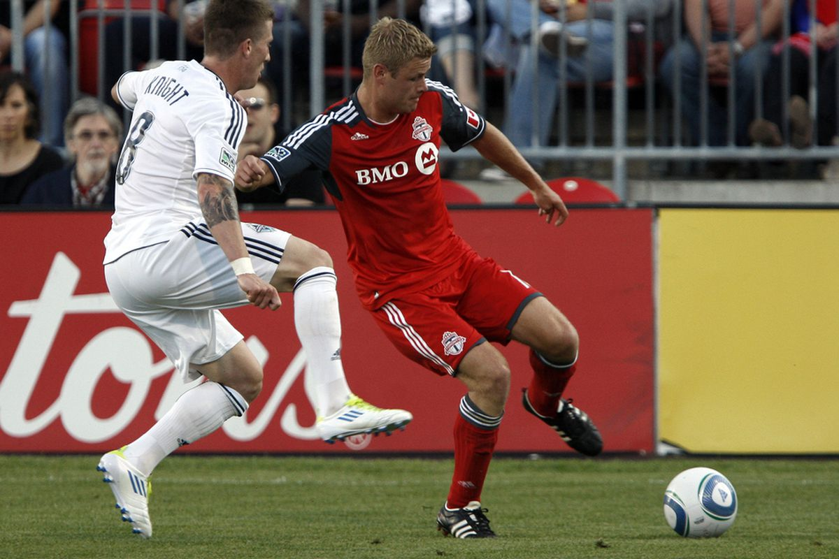 TORONTO, CANADA - JUNE 29: Nick Soolsma #18 of Toronto FC gets stopped by Wes Knight #8 of Vancouver Whitecaps FC during MLS action at BMO Field June 29, 2011 in Toronto, Ontario, Canada. (Photo by Abelimages/Getty Images)