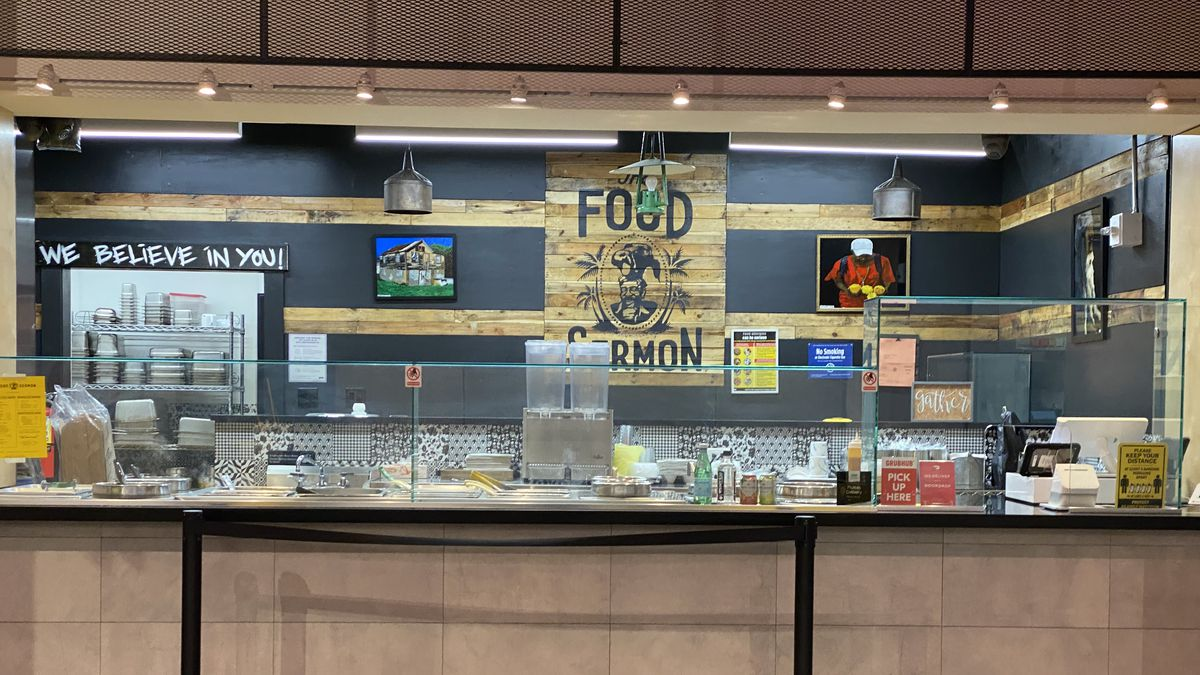 """An empty counter at the Food Sermon, with a sign that reads: """"We believe in you,"""" hanging in the back"""