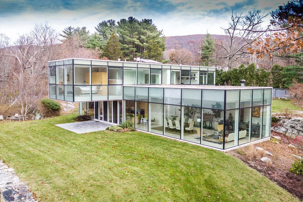 Glass house formed by two rectangular volumes. The upper level is placed perpendicularly to the lower one and cantilevers above it.