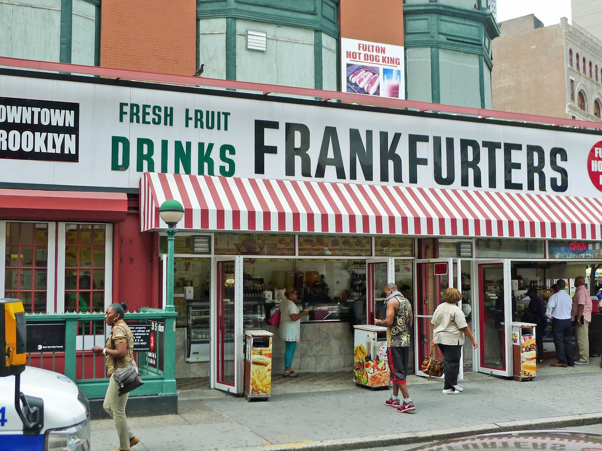 Fulton Hot Dog King Brooklyn, with a giant sign that says Frankfurters and open sides on the corner.