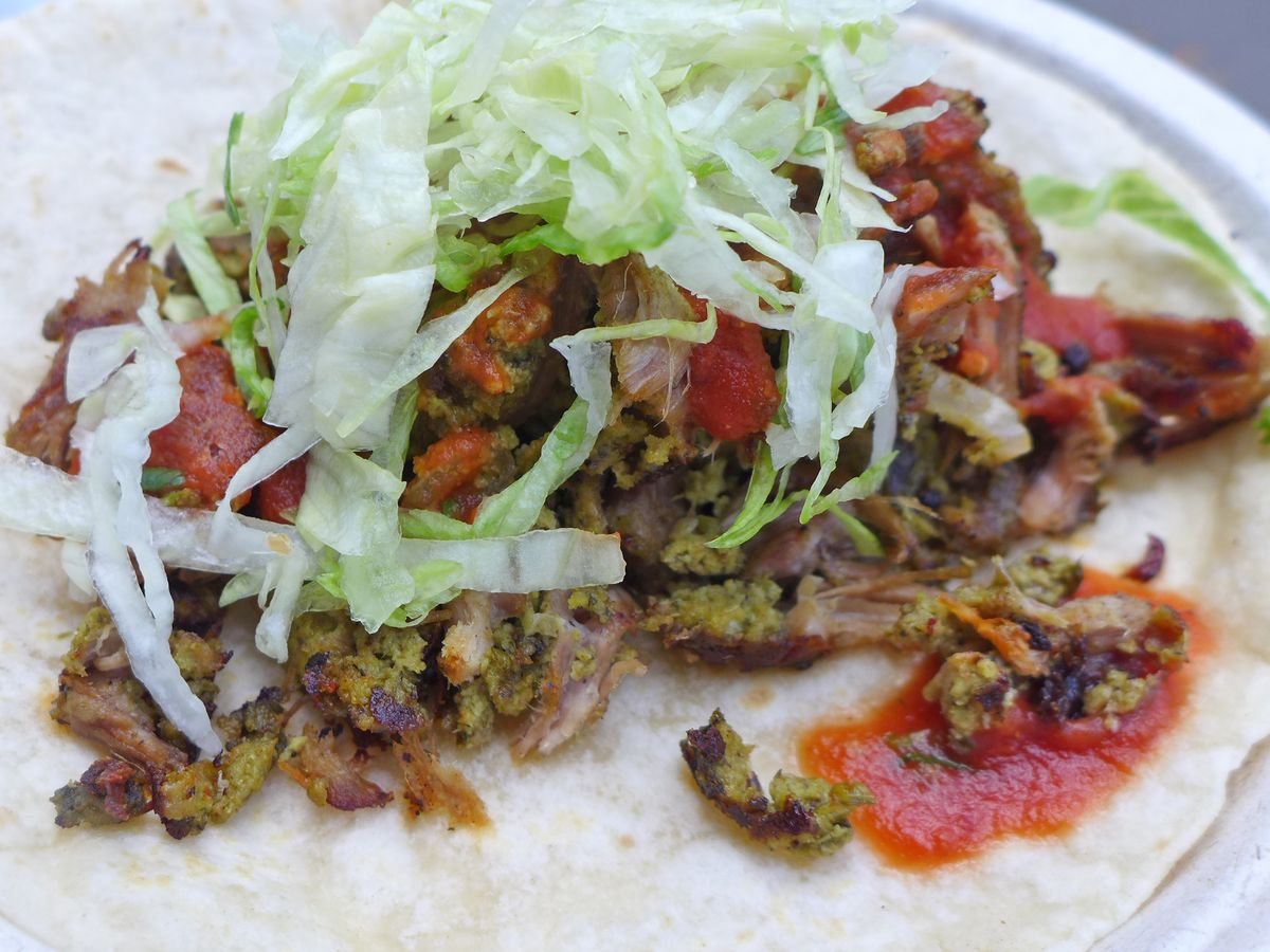 A big flour tortilla with chunks of pork and splotches of red sauce.