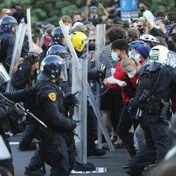 Police confront protesters decrying the police shooting of Bernardo Palacios-Carbajal in Salt Lake City on Thursday, July 9, 2020.