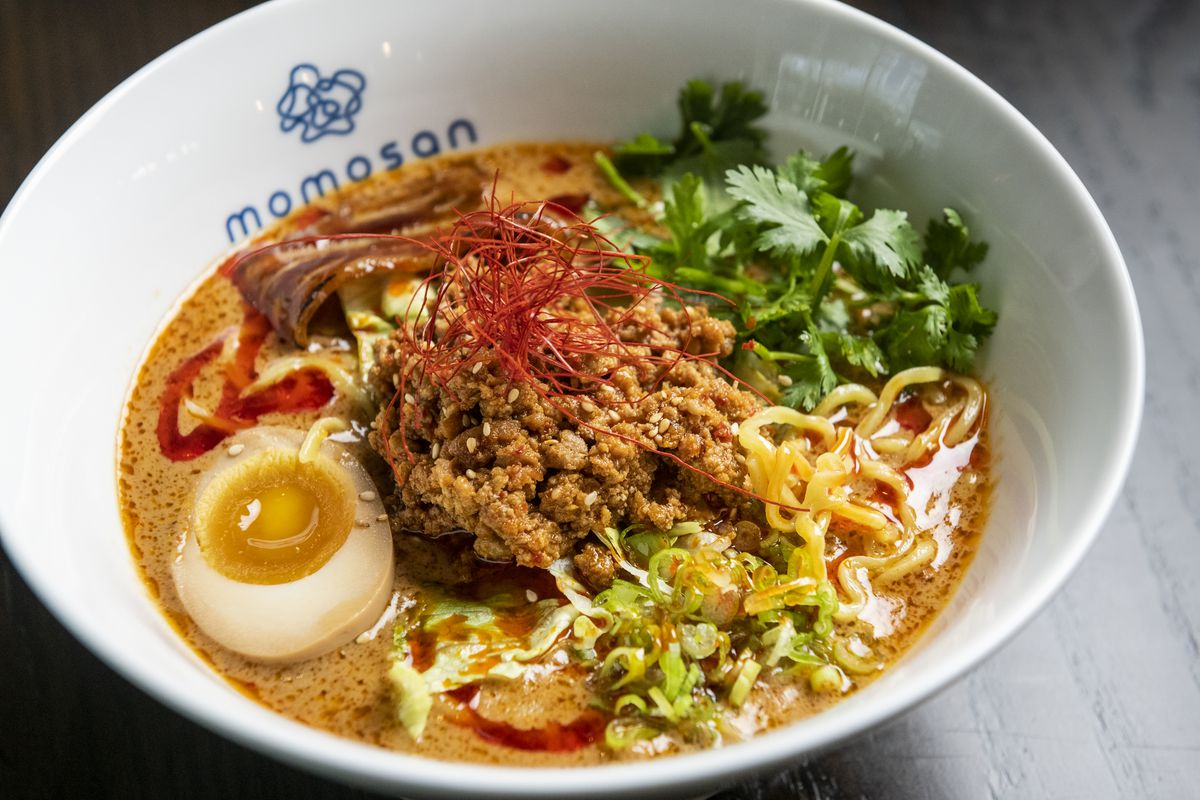 Closeup shot of a bowl of ramen with ground pork, a thick yellow-orange broth, a runny egg, and other toppings.