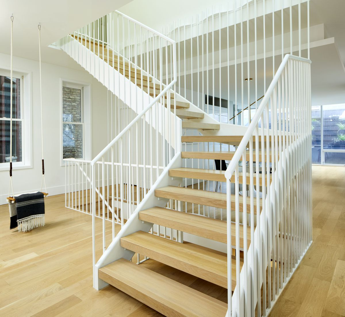 A stairwell is topped by a skylight. The stairs have no treads and the metal rails are thin, this allows natural light to filter to the basement.