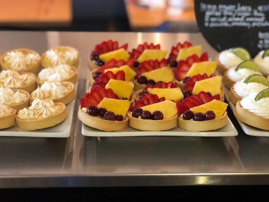 Trays of fruit-topped tarts on a bakery counter