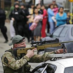 A sharpshooter trains his sight on a building as neighborhood residents stand on the street while searching for a suspect in the Boston Marathon bombings in Watertown, Mass., Friday, April 19, 2013.Two suspects in the Boston Marathon bombing killed an MIT police officer, injured a transit officer in a firefight and threw explosive devices at police during their getaway attempt in a long night of violence that left one of them dead and another still at large Friday, authorities said as the manhunt intensified for a young man described as a dangerous terrorist. (AP Photo/Charles Krupa)