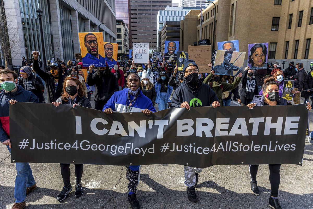 "A dense, but socially distanced crowd carries paintings of George Floyd and Breonna Taylor behind a line of masked protesters who, together, are carrying a banner that reads, ""I can't breathe, justice for George Floyd, justice for all stolen lives."""