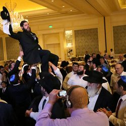 Male wedding guests lift the groom, Rabbi Mendy Cohen, on a chair during a traditional Chabad Lubavitch Jewish wedding at the Grand America Hotel in Salt Lake City on Monday, Sept. 12, 2016. Men and women celebrate separately.
