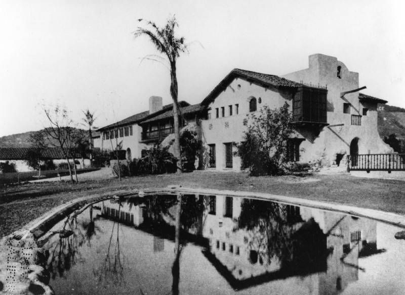 A large house. There is a body of water and a lawn in front of the house.